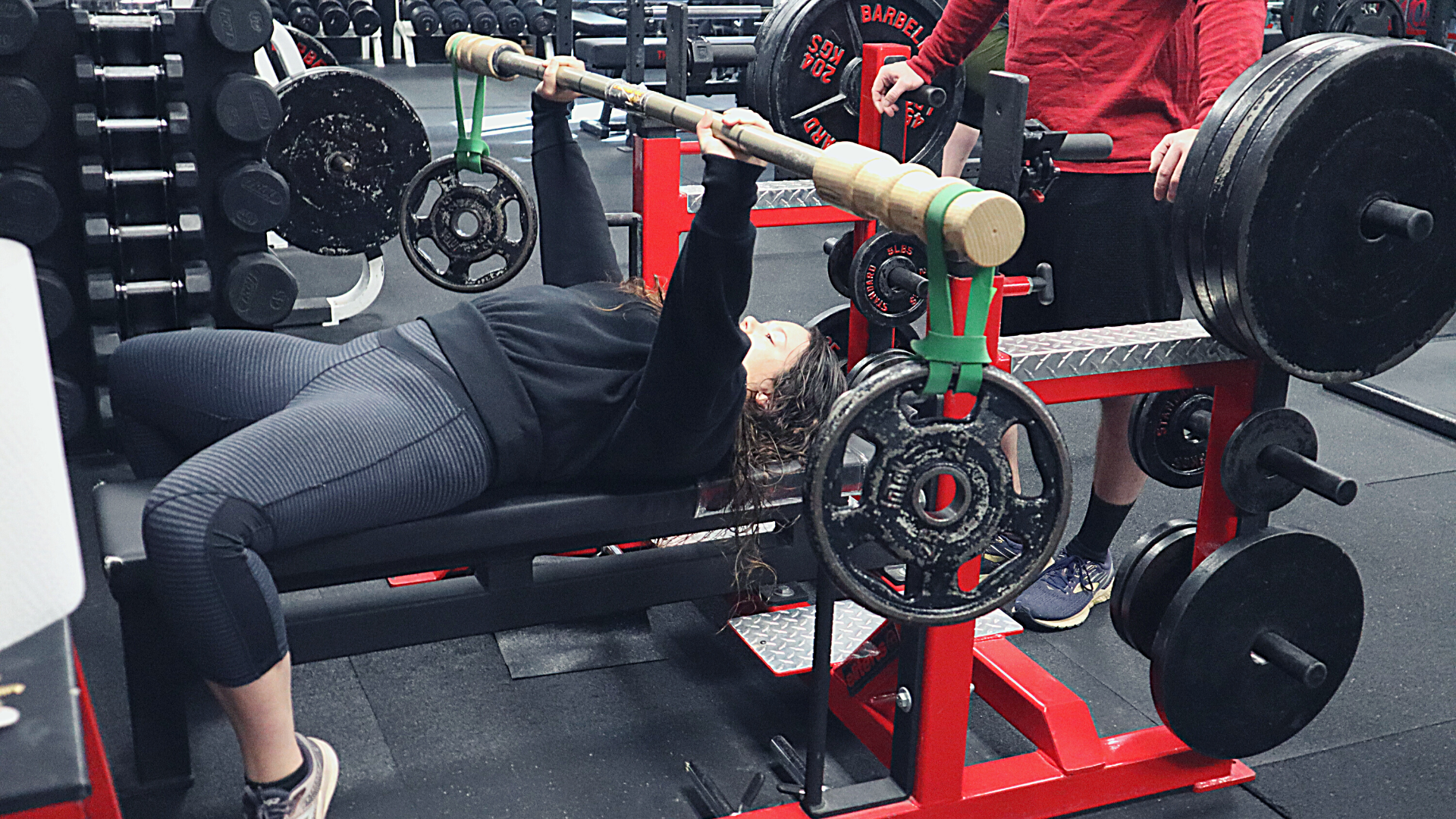 Female Performing Bench Press With Specialty Bar