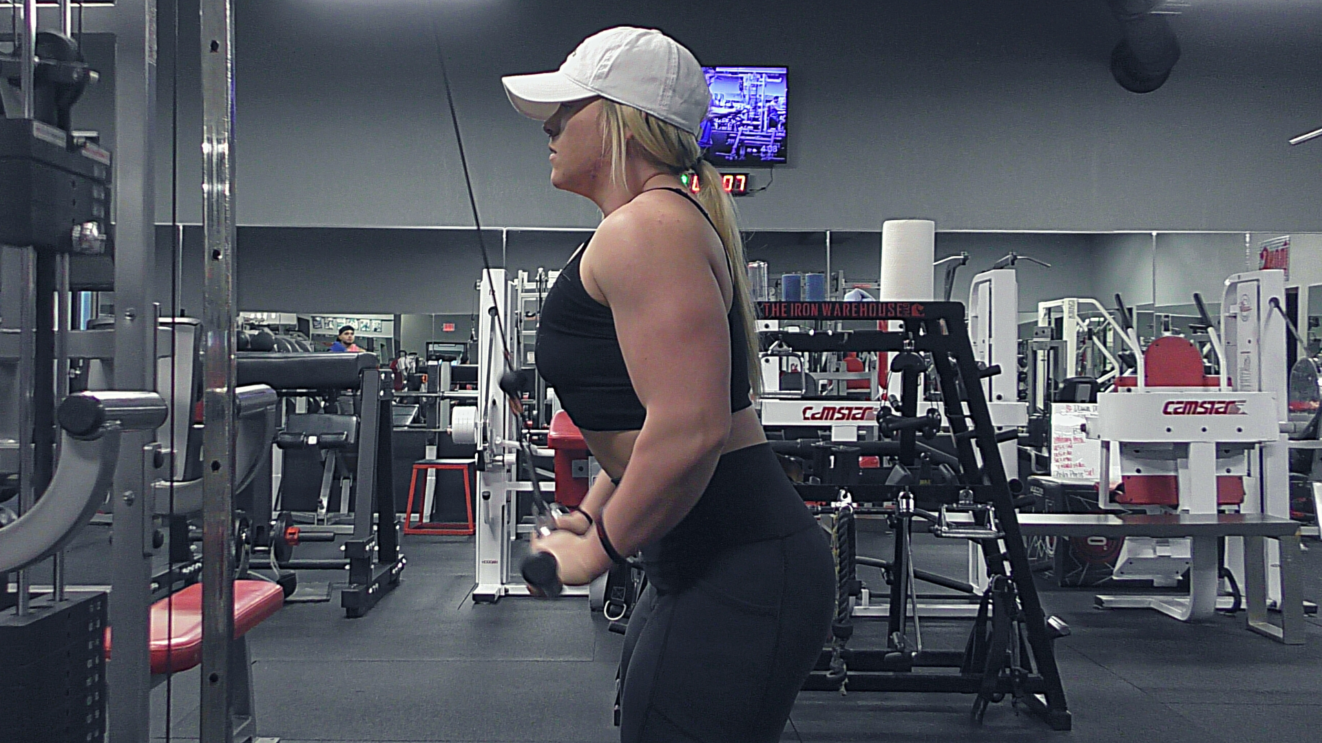Blonde Woman doing tricep pressdowns in the gym.
