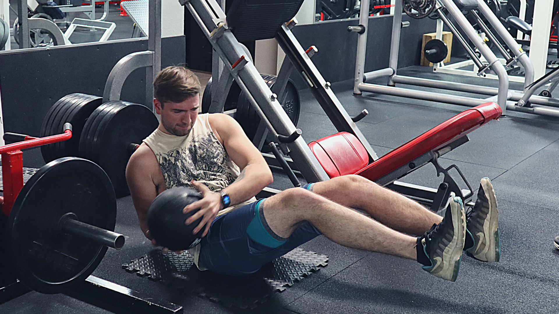 Young man doing russian twists with medicine ball