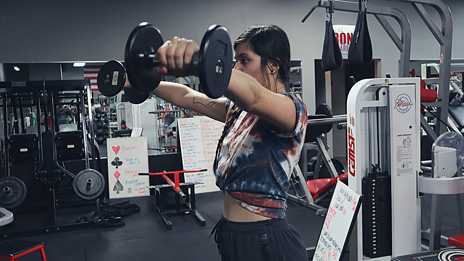 Female performing dumbbell lateral raises