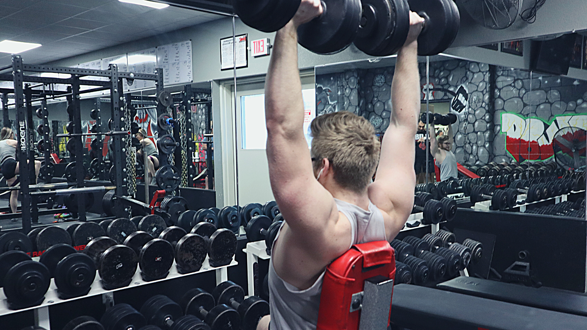 Young man doing dumbbell military press